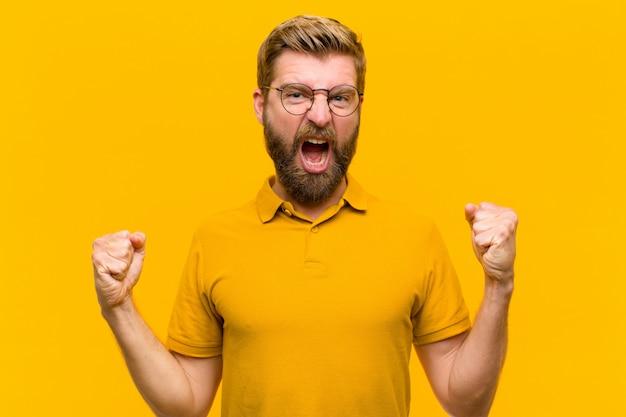 Молодой белокурый мужчина агрессивно кричит с сердитым выражением лица или сжал кулаки, празднуя успех у оранжевой стены