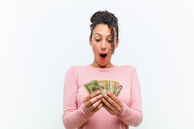 白い壁に紙幣を持つ若いきれいな女性