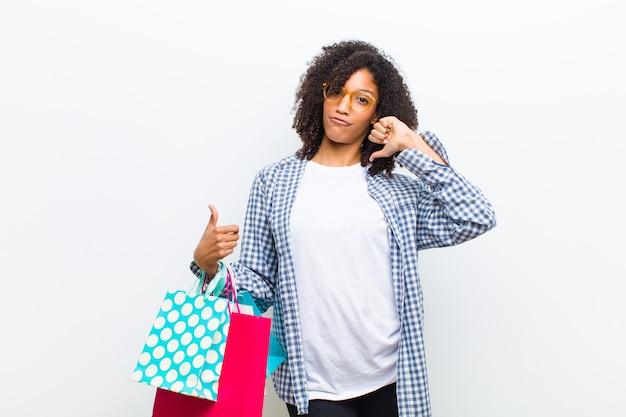 白い壁に買い物袋を持つ若いかなり黒人女性