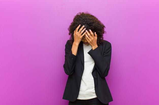 Молодая черная деловая женщина закрыла глаза руками с грустным, разочарованным взглядом отчаяния, плача, вид сбоку