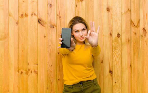 木製の壁に携帯電話で若いかなりブロンドの女性