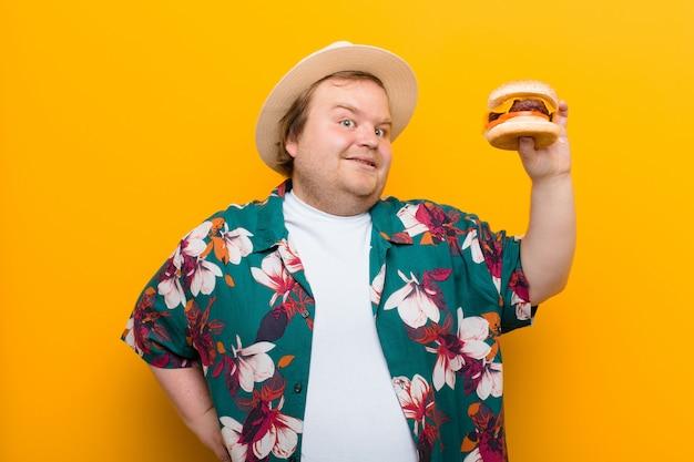 平らな壁にチーズハンバーガーを持つ若い大きなサイズの男