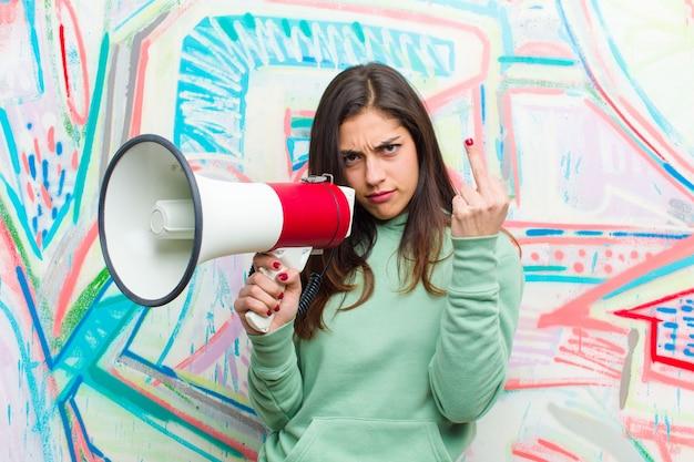 落書きの壁にメガホンを持つ若いきれいな女性