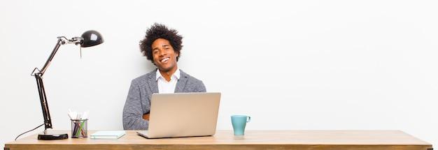 腕を組んで机の上に笑みを浮かべて幸せ、誇りと満足の達成者のように見える若い黒ビジネスマン