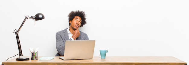 Молодой темнокожий бизнесмен, думающий, чувствующий себя сомнительным и растерянным, с разными вариантами, задающийся вопросом, какое решение принять на столе