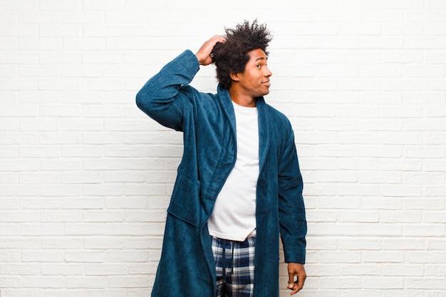 Молодой темнокожий мужчина в пижаме с платьем, чувствуя себя озадаченным и растерянным, почесывая голову и глядя в сторону