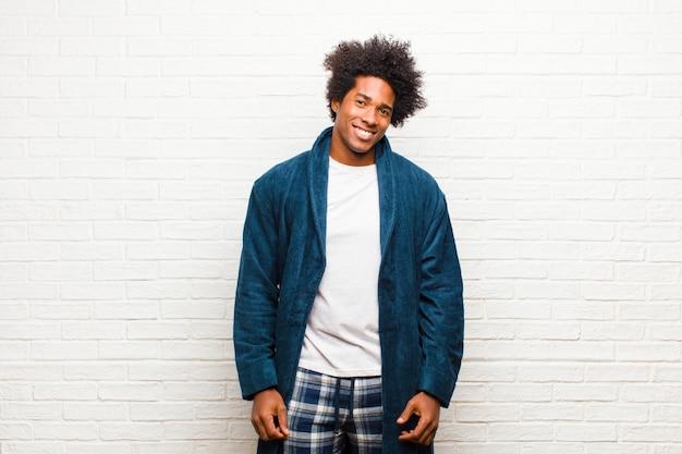 Молодой темнокожий мужчина в пижаме с платьем выглядит гордым, уверенным, крутым, дерзким и высокомерным, улыбающимся, чувствуя себя успешным