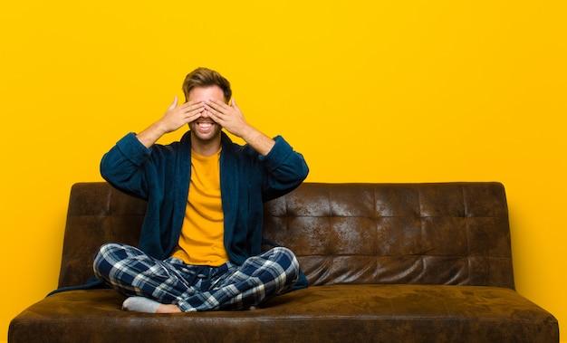 笑みを浮かべて幸せを感じ、両手で目を覆って信じられない驚きを待っているパジャマを着た若い男。ソファに座って