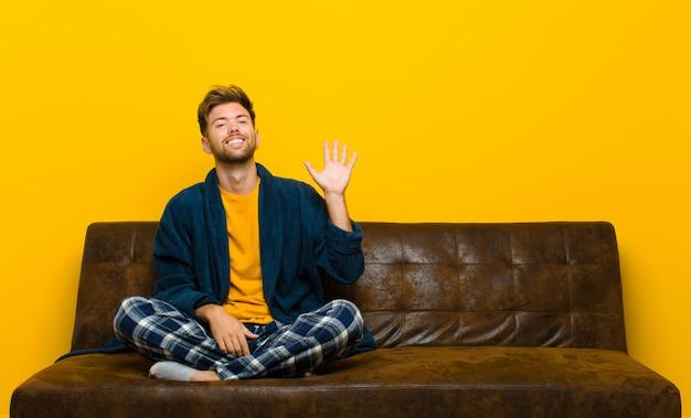 パジャマを着た若い男が喜んで元気よく笑って、手を振って、あなたを歓迎して挨拶するか、さようならを言います。ソファに座って