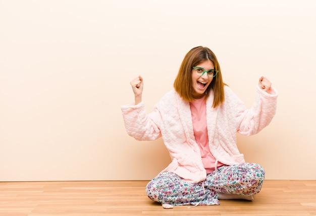 自宅で座っているパジャマを着ている若い女性は幸せ、肯定的かつ成功を感じて、勝利、成果または幸運を祝う