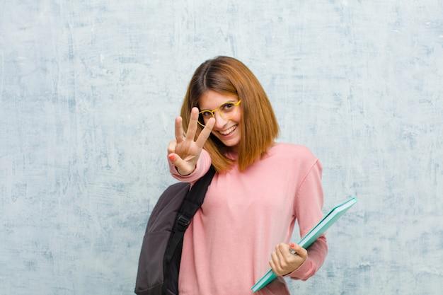 Молодой студент женщина улыбается и смотрит дружелюбно, показывая номер три или третий с рукой вперед, считая вниз