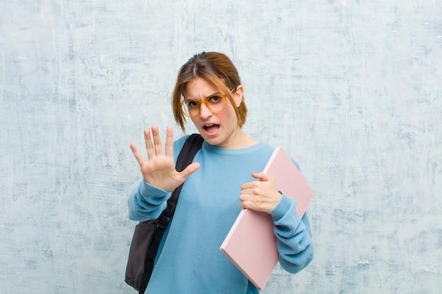 恐怖を感じ、後退し、恐怖とパニックで叫んで、悪夢に反応する若い学生女性