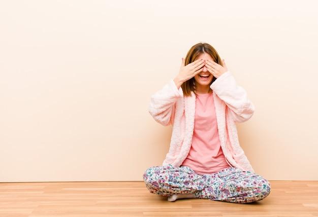 笑みを浮かべて、幸せな気分で座って、両手で目を覆って、信じられない驚きを待っているパジャマを着ている若い女性