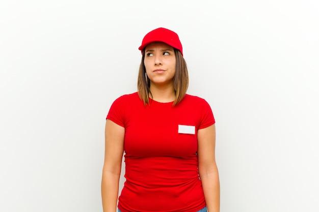 Доставщица выглядит озадаченной и растерянной, удивляясь или пытаясь решить проблему или думая