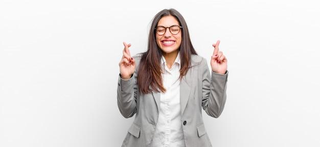若いきれいな女性の笑みを浮かべて、両方の指を心配そうに交差、心配と希望または幸運を願って感じ