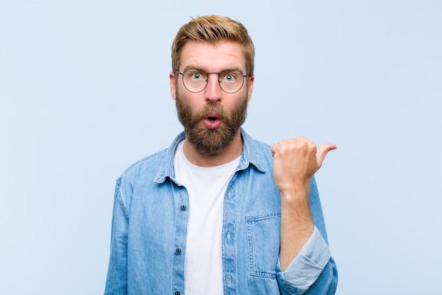 Молодая блондинка взрослый мужчина, удивленный недоверием, указывая на объект на боку и говоря «вау», невероятно