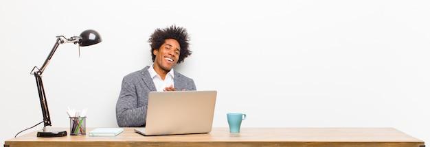ロマンチックな幸せ、そして恋を感じている若い黒人実業家、元気に笑顔と机の上の心に近い手を繋いでいます。