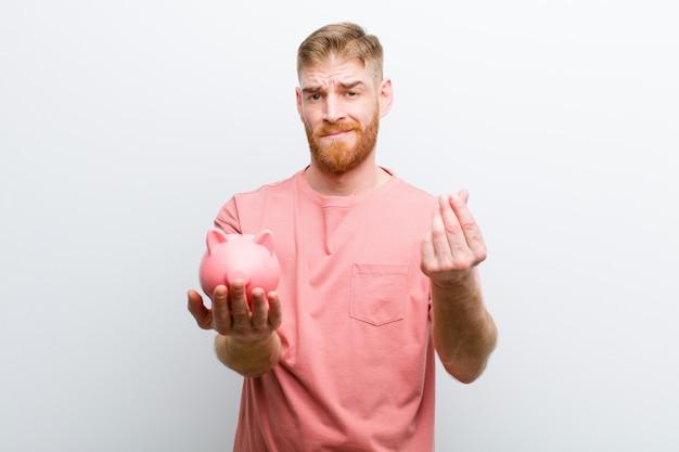 Молодой рыжий мужчина держит копилку