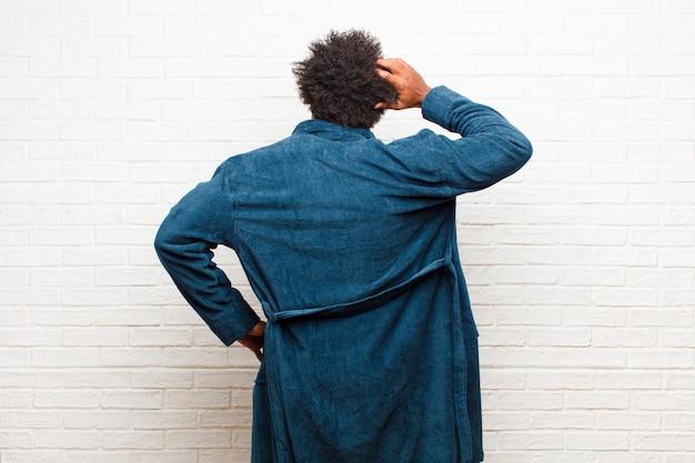 Молодой темнокожий мужчина в пижаме с платьем, чувствуя себя невежественным и растерянным, думая о решении, с рукой на бедре и другим на голове, вид сзади