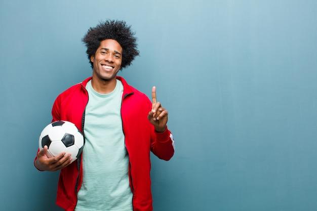 Молодой черный спортивный человек с футбольным мячом