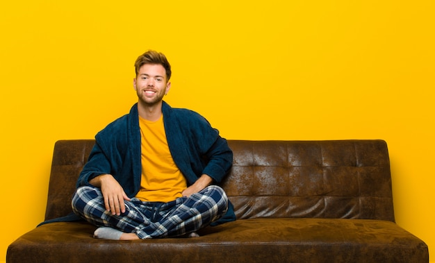 ヒップと自信を持って、肯定的で、誇りに思って、フレンドリーな態度に手で幸せそうに笑ってパジャマを着ている若い男。ソファに座って