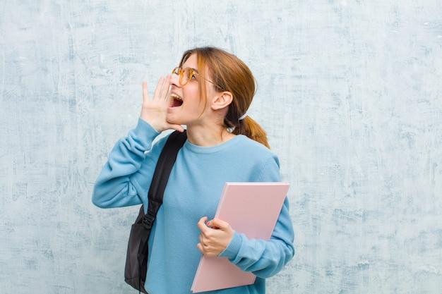 口の横に手で、側にスペースをコピーするために大声で怒って叫んで若い学生女性