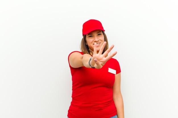 Доставка женщина улыбается и выглядит дружелюбно, показывая номер четыре или четвертый с рукой вперед, считая вниз