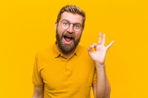 若いブロンドの男は成功と満足を感じて、口を大きく開けて笑みを浮かべて、手でいい兆候を作る