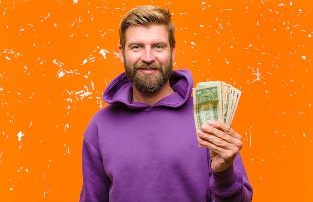 ドル紙幣や紫色のパーカーを着ている紙幣を持つ若い金髪男