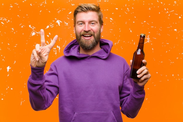 紫色のパーカーを着てビールを持つ若い金髪男