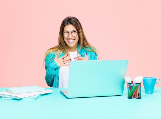 幸せ、驚き、誇りに思って、興奮して、自己を指しているラップトップで働く若いきれいな女性