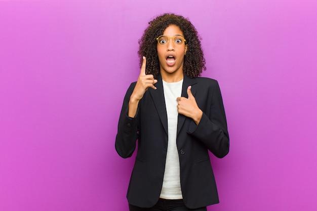 若い黒人ビジネス女性の誇りと驚きを感じて、自信を持って自己を指して、成功したナンバーワンのような感じ