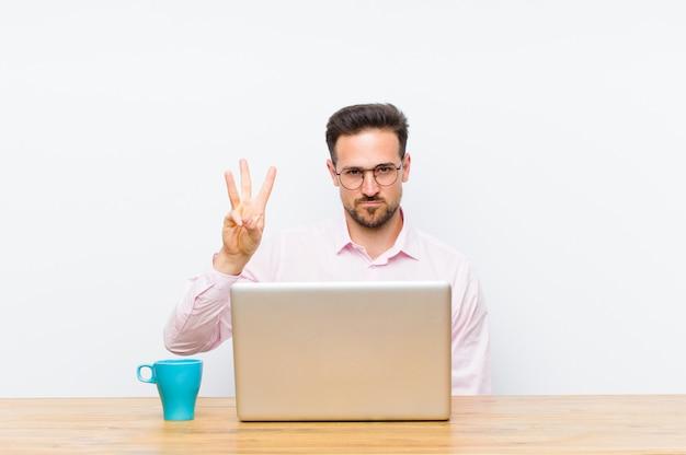 Молодой красивый бизнесмен улыбается и смотрит дружелюбно, показывая номер три или третий рукой вперед, считая вниз