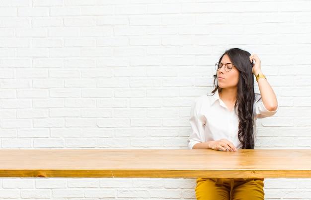 Молодая симпатичная латинская женщина чувствует себя озадаченной и смущенной, почесывая голову и глядя в сторону, сидя перед столом