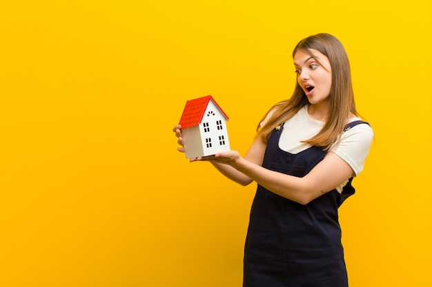 家のモデルを持つ若いきれいな女性