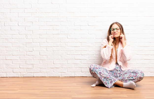 怒って、ストレスを感じ、イライラして、耳をつんざくようなノイズ、音、または大きな音楽に覆われている若いきれいな女性。ホームコンセプト