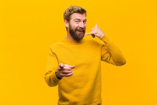 陽気な笑顔と電話で話している後ジェスチャーを呼び出しながら指している若い金髪男