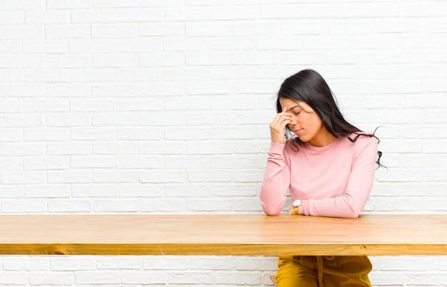 ストレス、不幸、欲求不満、額に触れると、テーブルの前に座っている激しい頭痛の片頭痛に苦しんでいる若いかなりラテン女性