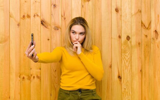 Молодая красивая белокурая женщина с мобильным телефоном против деревянной стены