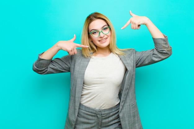 自信を持って自分の広い笑顔を指している若いかなりブロンドの女性