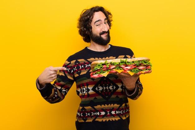 巨大なサンドイッチと狂気の若いひげを生やした男。