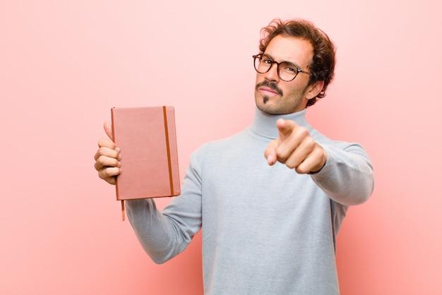 ピンクの平らな壁にメモ帳で若いハンサムな男