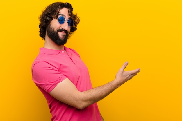 笑みを浮かべて、あなたに挨拶し、成功した取引、オレンジ色の壁に対する協力の概念を閉じるために手を振るを提供する狂った若者