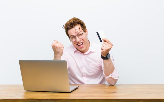 クレジットカードで彼の机で働く若い赤ヘッド実業家