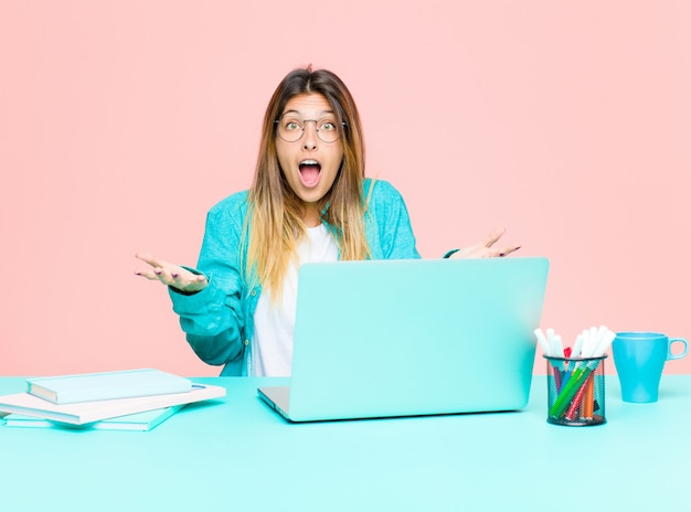 非常にショックと驚き、不安とパニックを感じ、ストレスと恐怖の表情でラップトップで働く若いきれいな女性