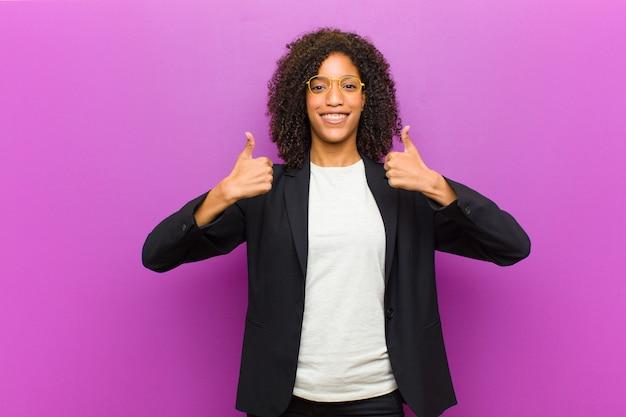 Молодая черная деловая женщина улыбается широко глядя счастливым, позитивным, уверенным и успешным, с обоими пальцами вверх