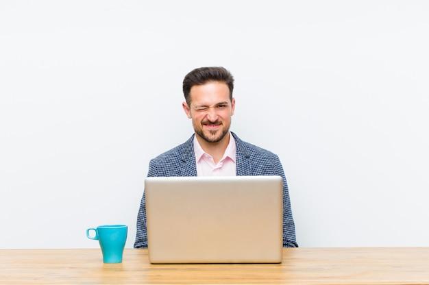 Молодой красивый бизнесмен выглядит счастливым и дружелюбным, улыбается и подмигивает вам с позитивным настроем
