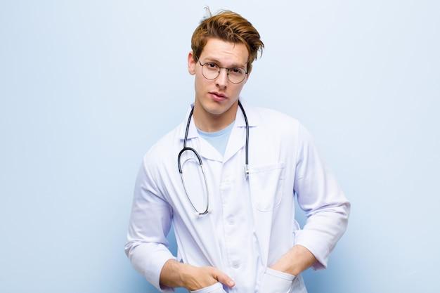 Молодой рыжий главный врач выглядит гордым, уверенным, крутым, дерзким и высокомерным, улыбающимся, чувствующим себя успешным на фоне синей стены