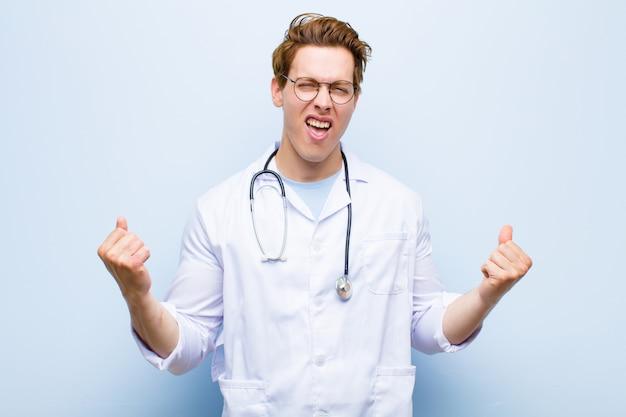 Молодой красный главный врач чувствует себя счастливым, позитивным и успешным, празднует победу, достижения или удачу на фоне синей стены