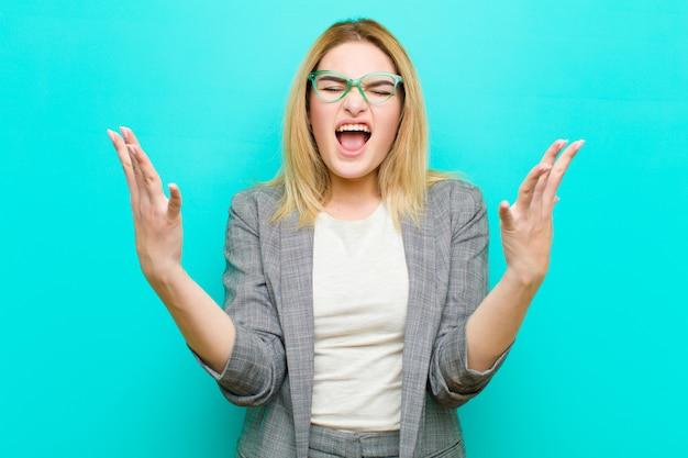 若いかなりブロンドの女性が猛烈に叫んで、ストレスを感じ、空中に手を挙げてイライラしている理由を言って